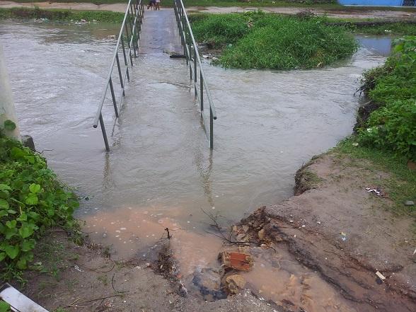 A ponte sobre o Riacho da Xoxota, no Jardim Universitário, desabou neste sábado pela manhã após ter a estrutura danificada devido à correnteza forte. (Foto: SE