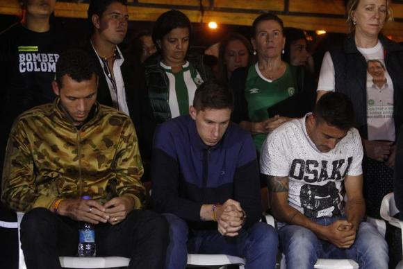 Sobreviventes do acidente aéreo da Chapecoense, Helio Zampier Neto, Alan Ruschel e Jackson Follman, em oração durante homenagem do município de La Unión/ Colômbia. (Foto: Luis Eduardo Noriega A./EFE)